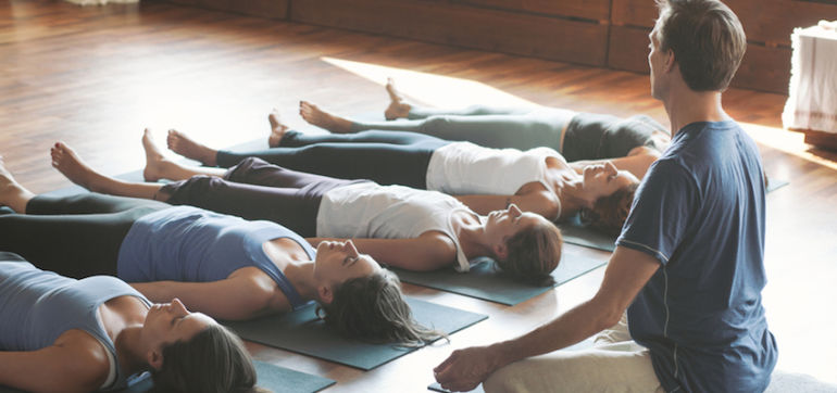 6 Reasons To Practice Yoga At A Studio (Instead Of With A Laptop) Hero Image