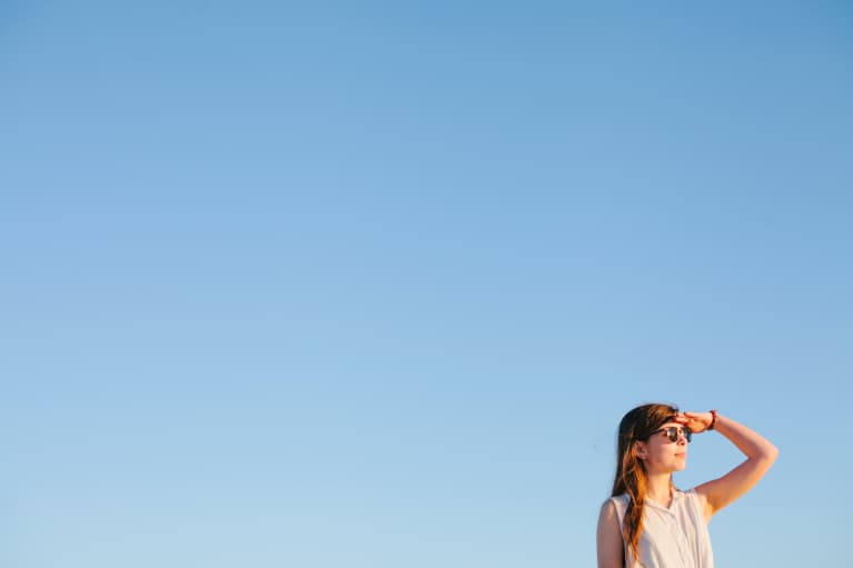 young white woman in sunglasses looking into distance with blue sky behind her