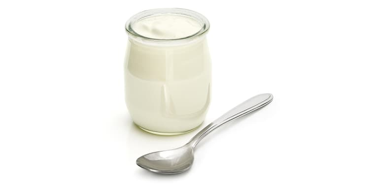 glass jar of plain greek yogurt with spoon over white background