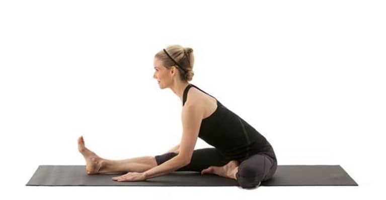 woman doing janu sirsasana or seated head to knee yoga pose