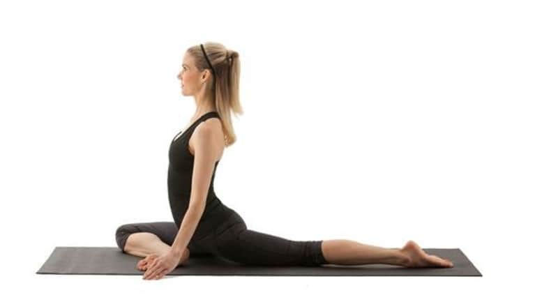 side view of blonde woman doing pigeon pose yoga