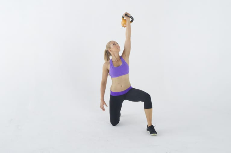 woman on one knee holding kettlebell above head with one hand
