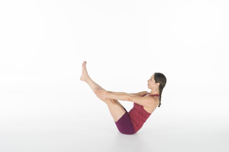 woman doing yoga boat pose or navasana