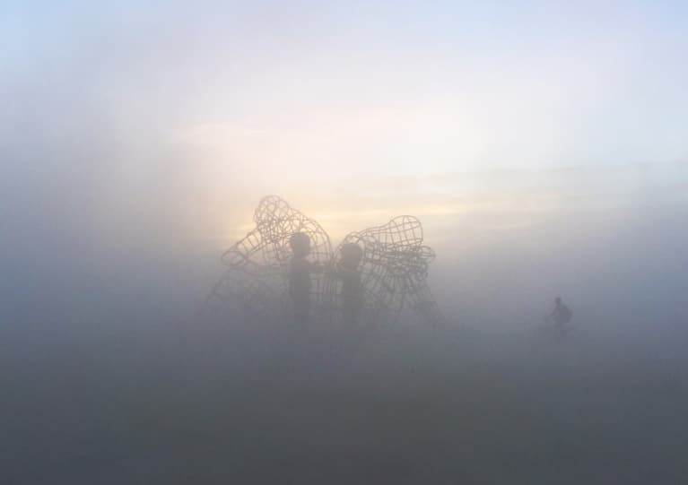 art installation at burning man with two adults facing away from each other with two children reaching towards each other