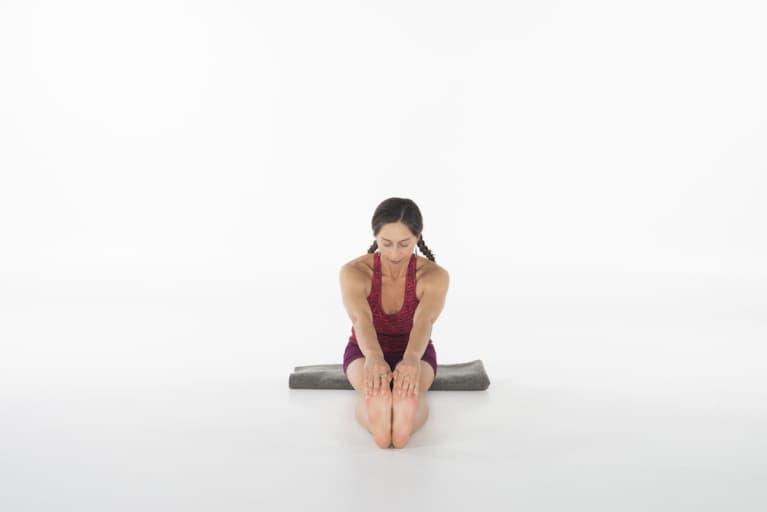 woman doing seated forward fold yoga pose facing camera