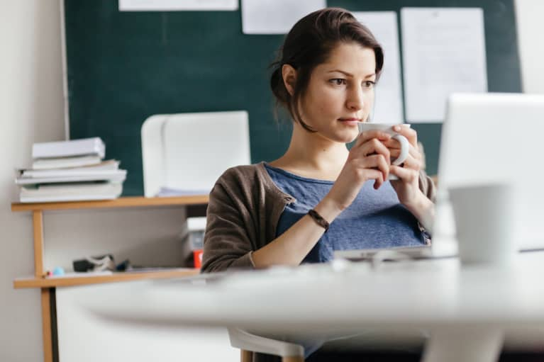woman sitting at her desk at work with coffee looking overwhelmed