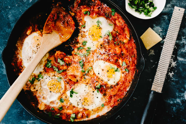 Shakshuka in an iron skillet with parmesan cheese and a cheese grater