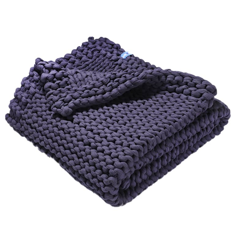 Navy blue, knitted weighted blanket, folded up.