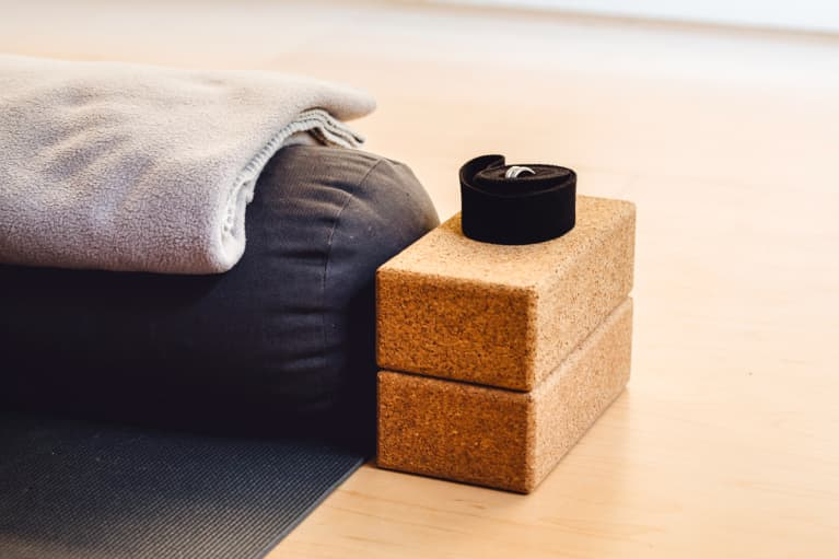 Composition of yoga brick, belt, mat and blanket placed on wooden floor in training room