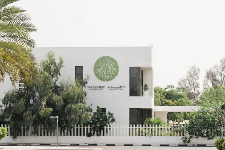 wellness center with green logo surrounded by trees