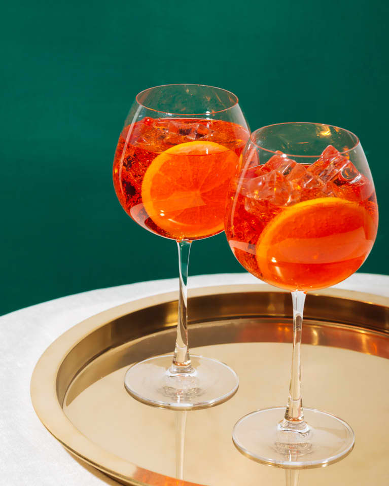 aperol spritz on a gold platter and green background