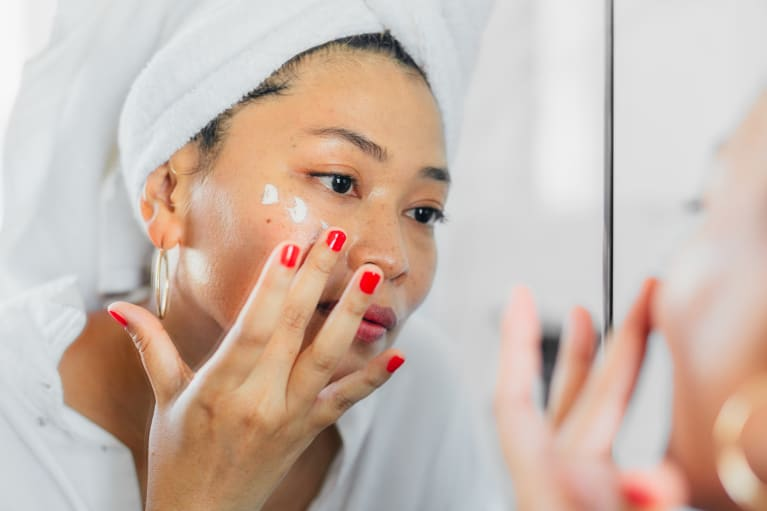 Woman in a Bath Towel Applying Moisturizer to Her Face