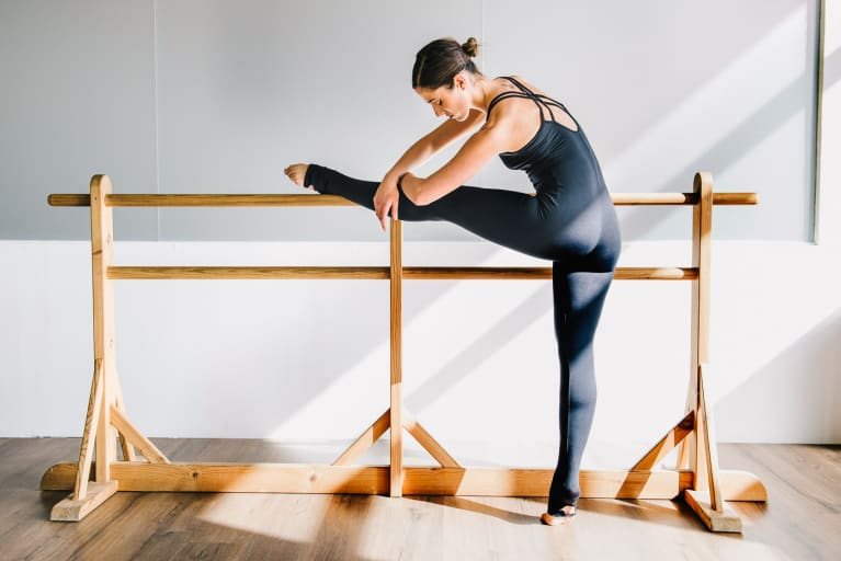 Woman Stretching on a Ballet Barre