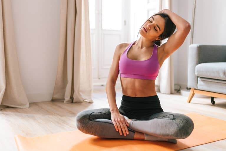 Brunette female with pink sports clothes stretching at home