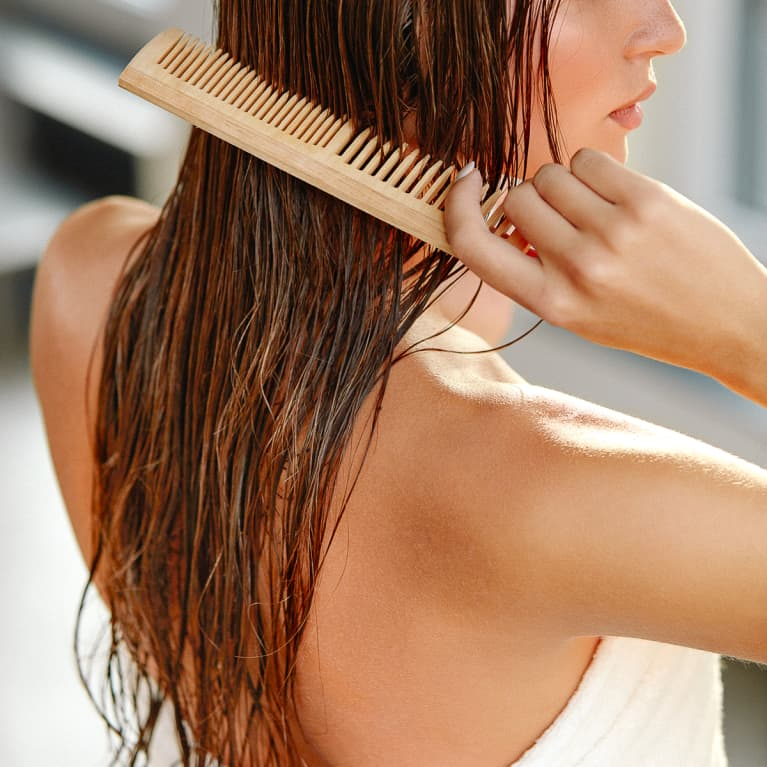 Woman Combing Her Wet Hair with a Wide Tooth Comb