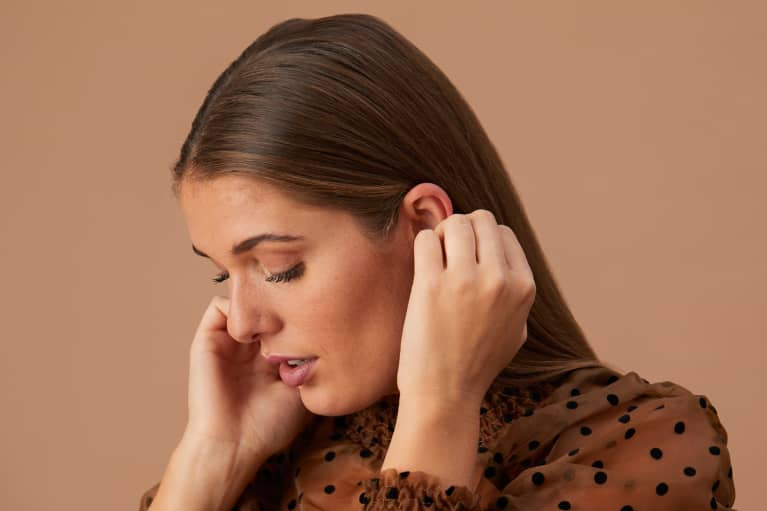 woman putting her hair behind her ears on brown background