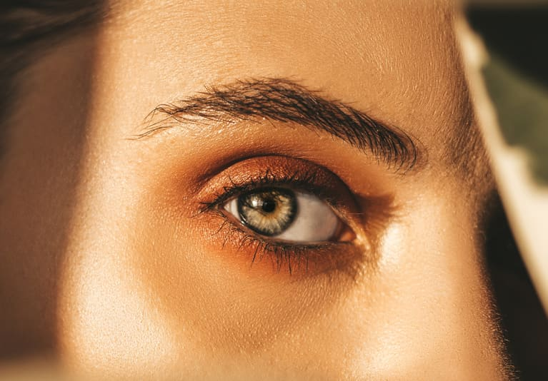 Woman with green eyes and full brows