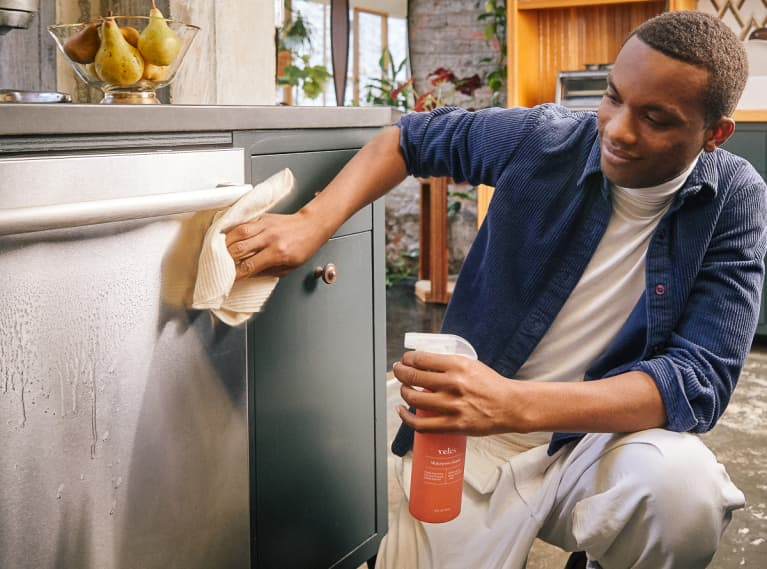 Man Wiping Down a Dishwasher with All Natural Household Cleaner