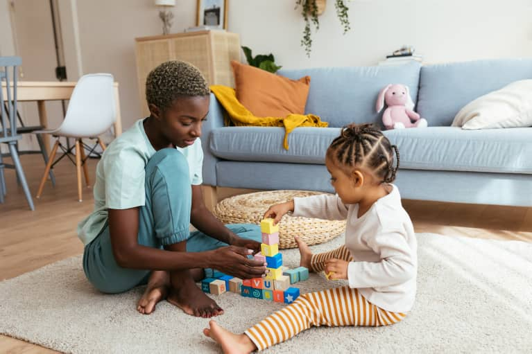 black mother playing with her young daughter using blocks