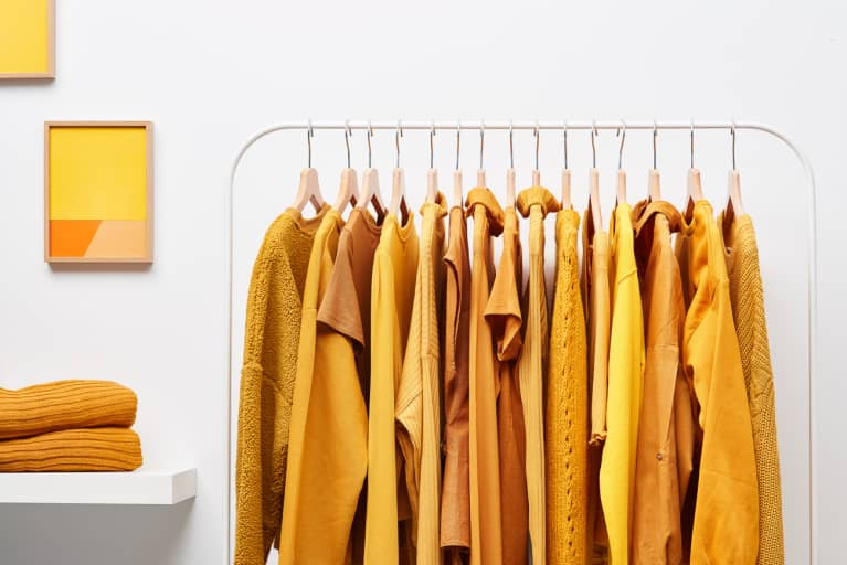Rack of bright yellow-colored clothing on rack in white wardrobe room