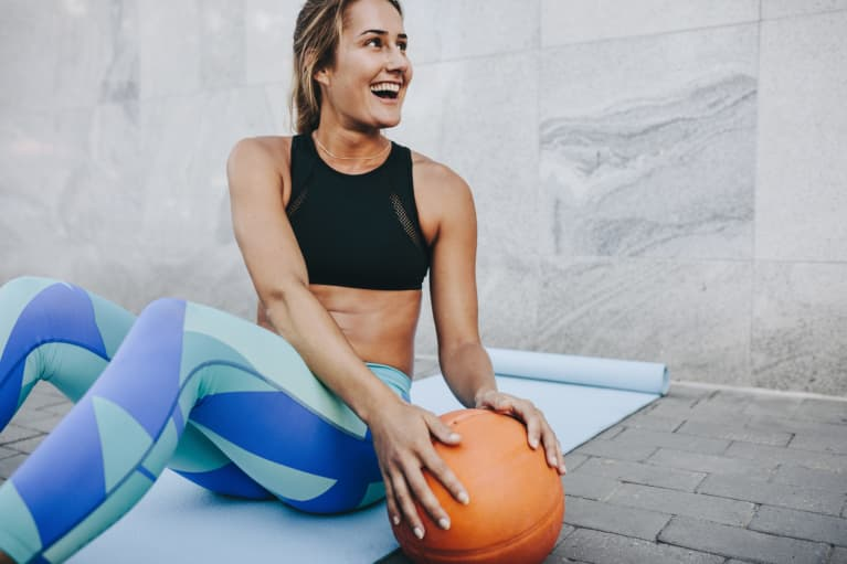 Smiling female athlete sitting on exercise mat doing sit ups holding a medicine ball
