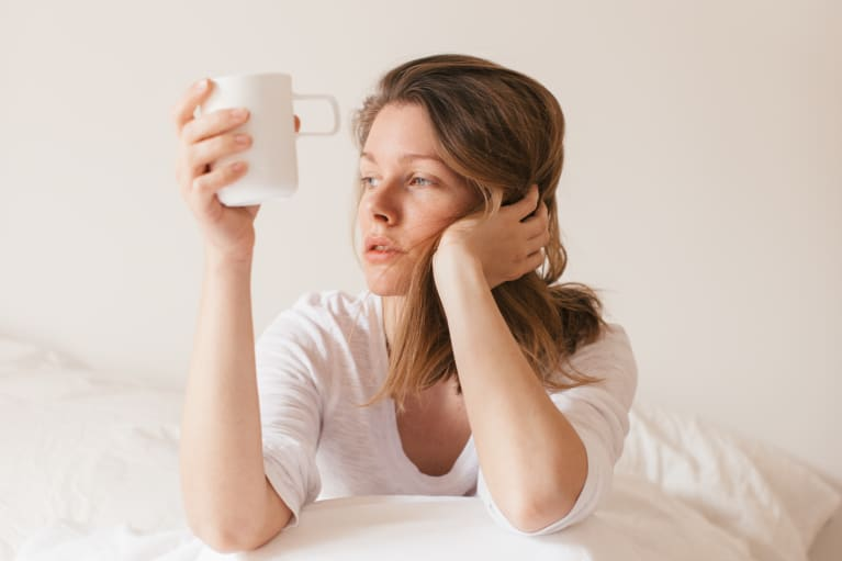 Tired Woman Sitting in Bed with Coffee Cup