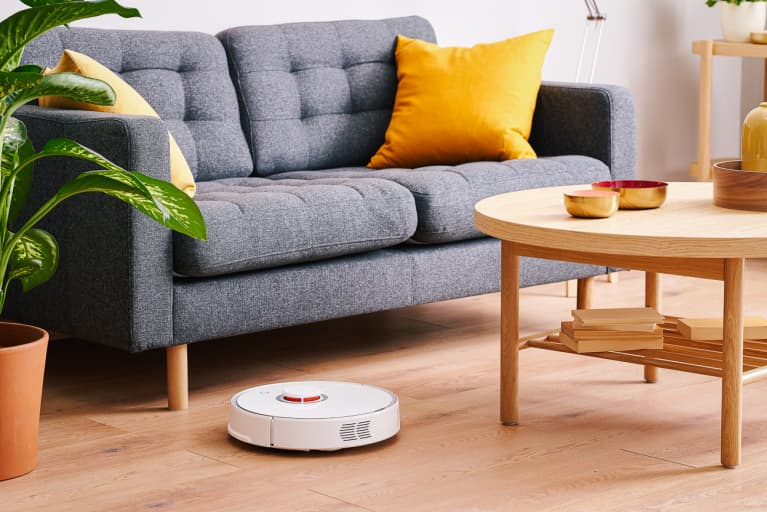 Contemporary robotic vacuum cleaner tidying laminate floor between sofa and table in modern apartment