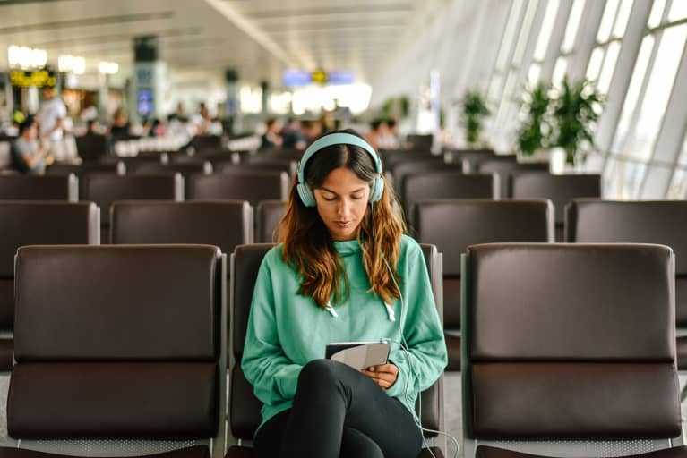 Woman Waiting in Airport Listening to Music