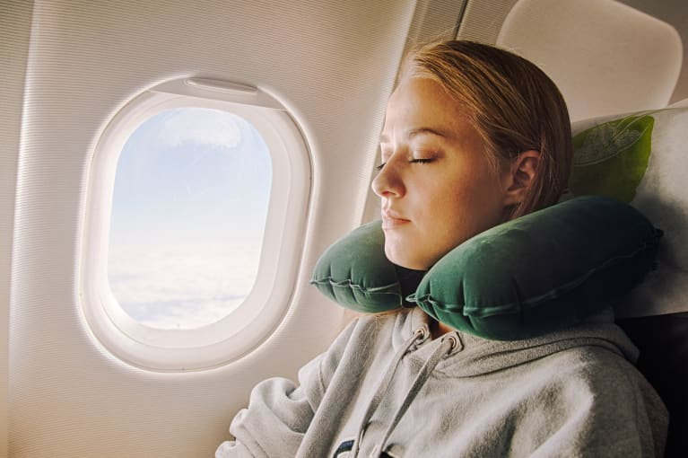 Woman Asleep on an Airplane with a Neck Pillow