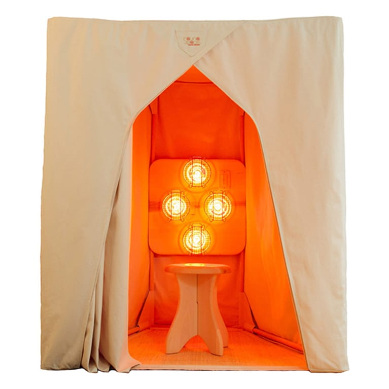 Portable infrared sauna with tan fabric tent and wooden bench