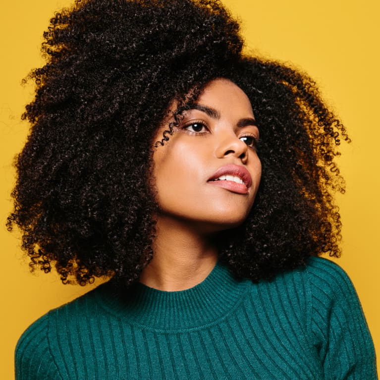 Young Woman with Natural Hair and Glowing Skin on a Yellow Background