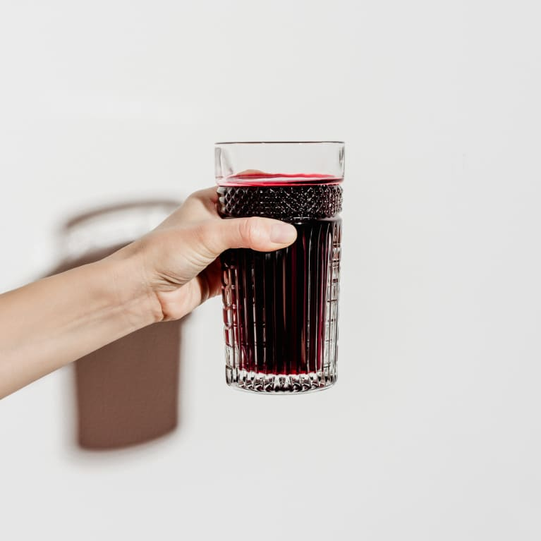Hand Holding a Glass of Freshly Squeezed Beet Juice