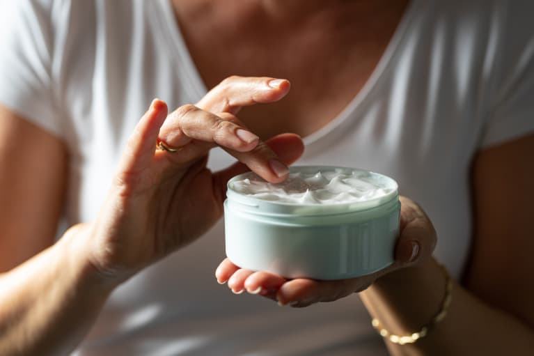 Picking facial cream with finger from a jar