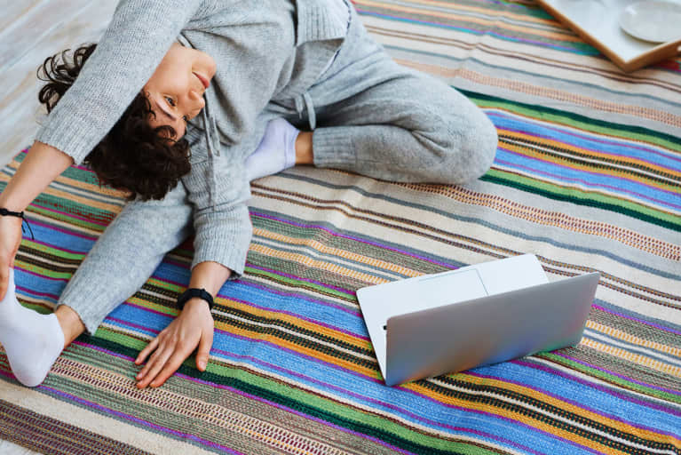 Woman stretching and doing yoga in front of computer laptop screen on rug indoors