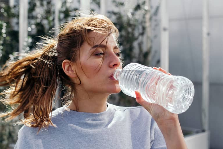 woman drinking from plastic water bottle after working out