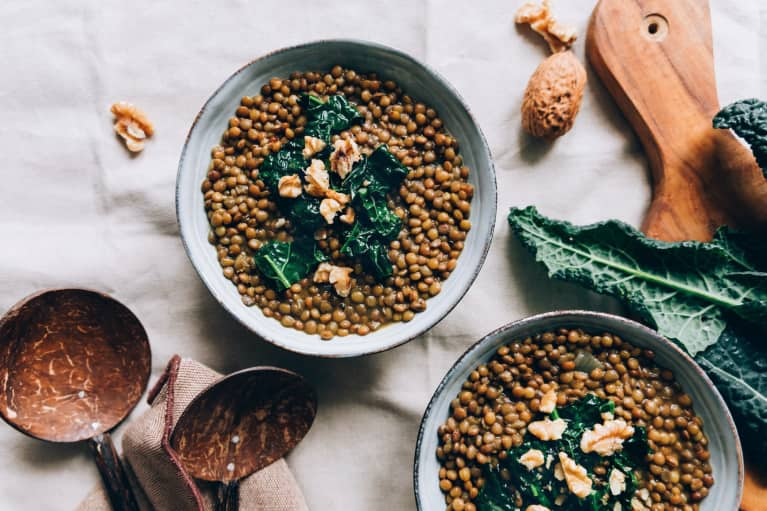 Still life of bowls of lentils with kale and walnuts on kitchen tablecloth / linen