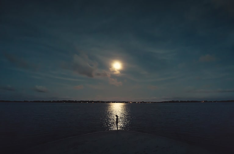 Young female silhouete at the shore with the reflected light of the moon on the sea