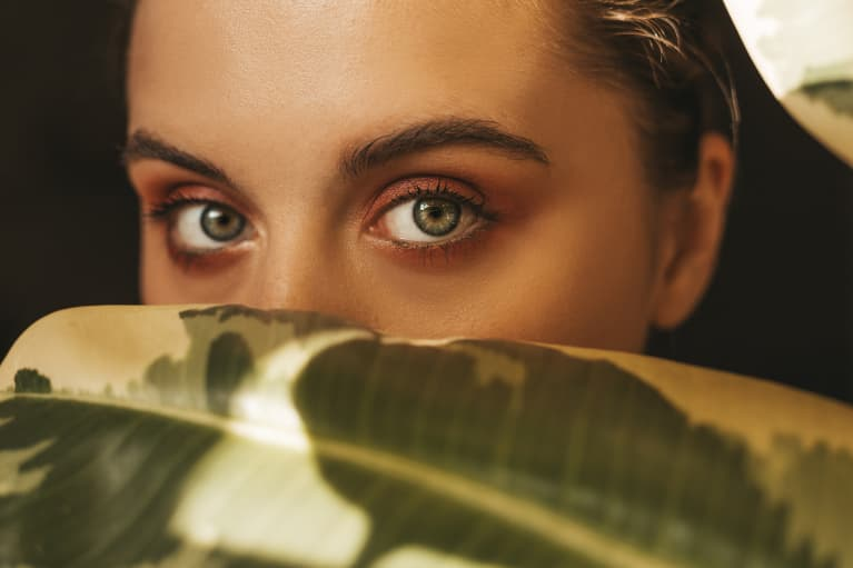 young woman with long eyelashes hiding behind a leaf