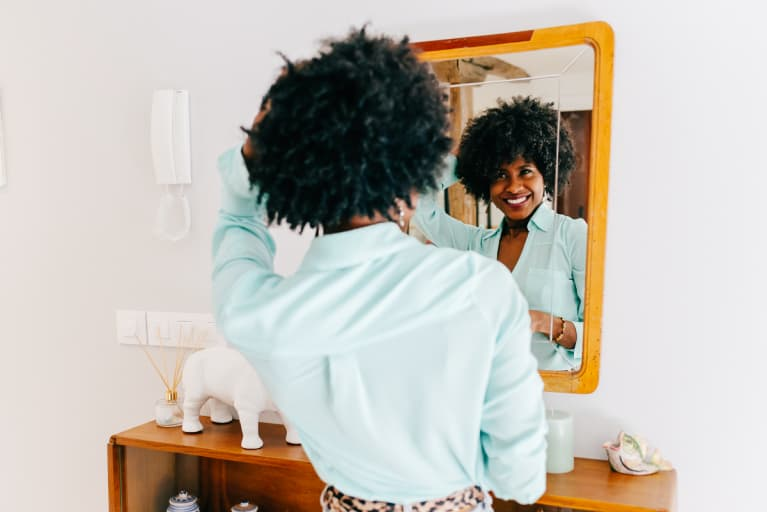 Smiling Woman Getting Ready in the Mirror