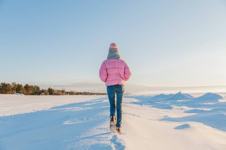 Woman in warm colorful clothes walking in the snow on a frosty sunny day