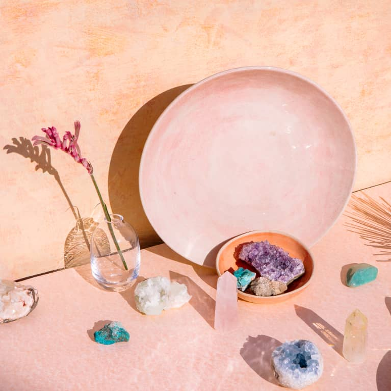 Bohemian chic decor style with collection of beautiful crystals, gemstones and objects on pale pink