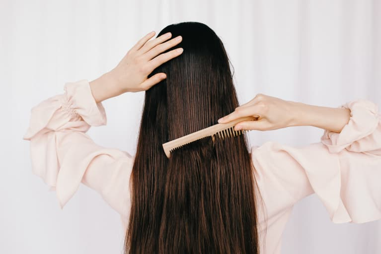 Back view of unrecognizable female combing and gently touching long hair against white background