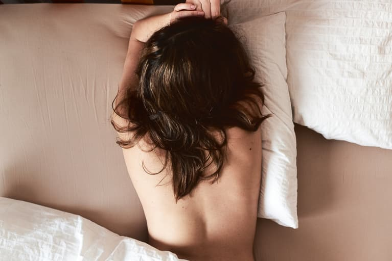 Long haired brunette lying face down on bed. Unrecognizable