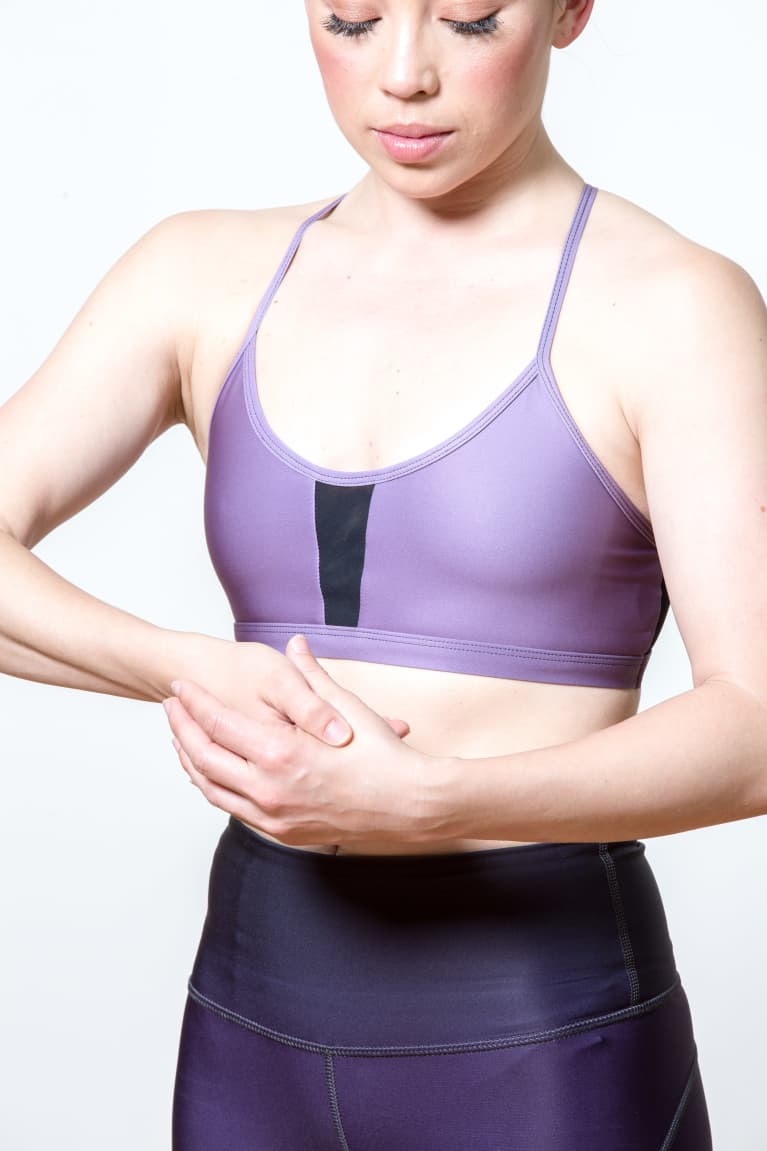 woman in athletic clothing pressing her hand