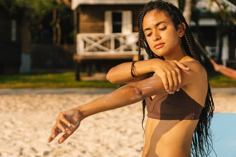 Young Woman Applying Sunscreen on a Beach