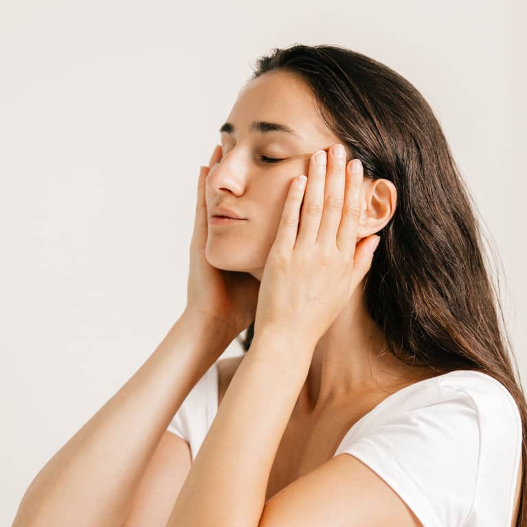 Young Woman Gently Massaging Her Face