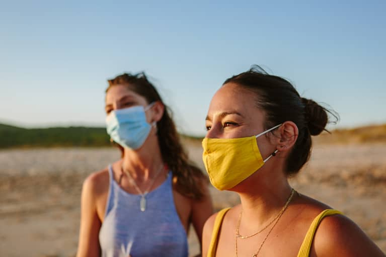 Two Women In Facemasks On The Beach