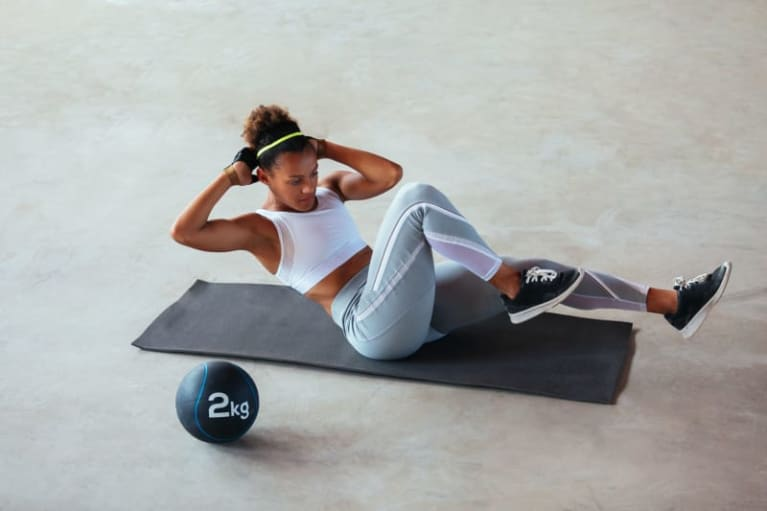 woman working out doing crunches on yoga mat