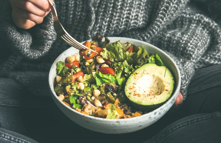 Woman eating fresh salad, avocado, beans and vegetables, square crop
