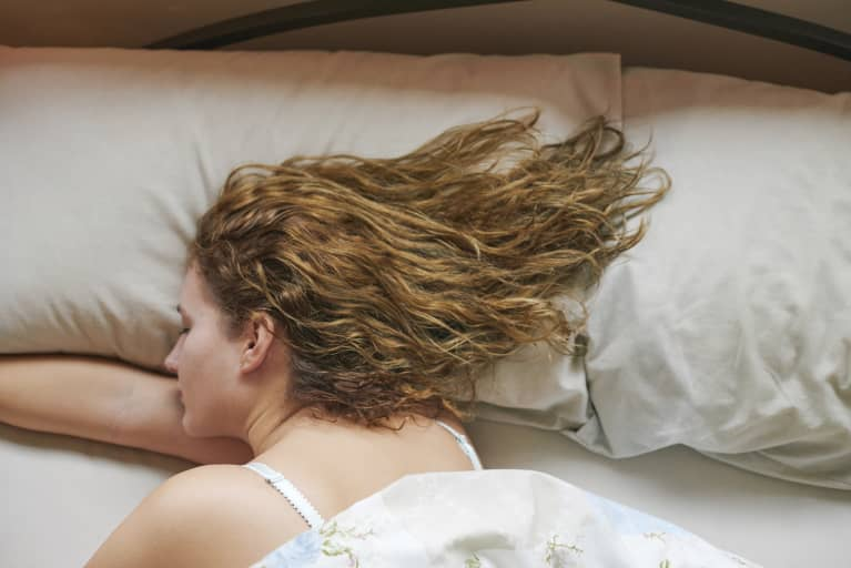Woman Sleeping with wavy hair spread across pillow